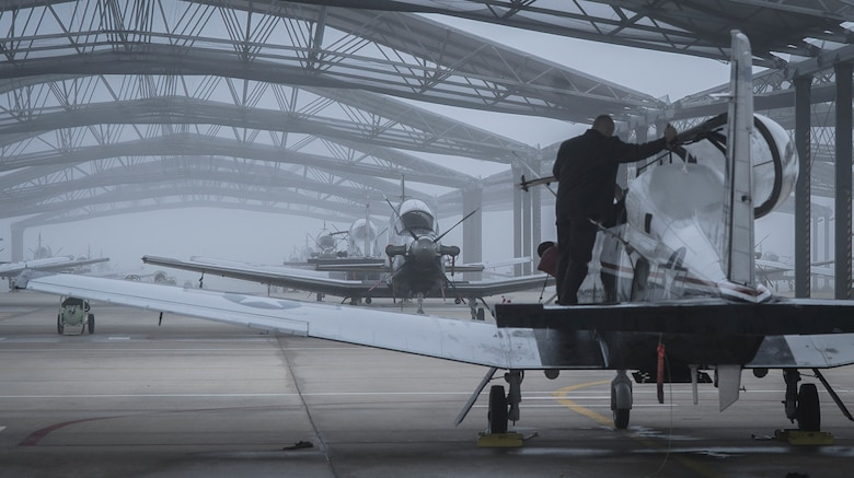 An L-3 Communications Holdings Inc. maintainer preps a T-6A Texan II as fog covers the flightline at Vance Air Force Base, Okla., Nov. 4, 2016. Since 1960, Vance AFB has been a joint civilian-military team, training more than 20,000 U.S. and allied nation pilots. (U.S. Air Force photo/David Poe)