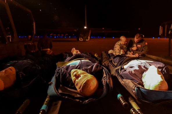 Simulated patients await evacuation as a team of medics from the 375th Aeromedical Evacuation Squadron discuss their plan to care for the patients during exercise Tropical Storm Greg, Nov. 8, 2016, at Alexandria, Louisiana.  The exercise was an example of how the U.S. Air Force provides support to local, state and federal authorities by performing a key role during crisis situations.  (U.S. Air Force Photo by Senior Airman Stephanie Serrano)