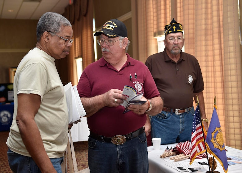 Pal Johnson, a U.S. Navy veteran, left, receives a briefing from Dean Nimocks, American Legion representative, during a veteran's appreciation event at the Red Bank Club here, Nov. 10, 2016. The inaugural appreciation day provided the opportunity for organizations such as Tricare, the American Legion and the 628th Medical Group to educate veterans and retirees about their benefits.