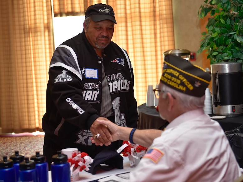 Clayton Givens, a U.S. Marine Corps veteran, left, shakes hands with Phil Cates, a U.S. Army veteran with the Ralph H. Johnson Veterans Association Medical Center, during a veteran's appreciation event at the Red Bank Club here, Nov. 10, 2016. The inaugural appreciation day provided the opportunity for organizations such as Tricare, the American Legion and the 628th Medical Group to educate veterans and retirees about their benefits.