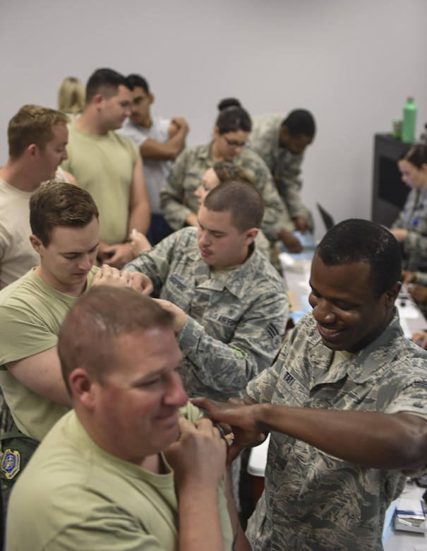 Members of Joint Base Charleston receive their annual flu vaccines from the 628th Medical Group (MDG) at a point of distribution during a public health emergency exercise on Joint Base Charleston, South Carolina, Nov. 9, 2016. In the event of a real world incident, members would be given a flu vaccine if they hadn't already received one, as well as medication to combat the outbreak. To simulate that, those who participated in the exercise were given the vaccination and candy to represent the medication.