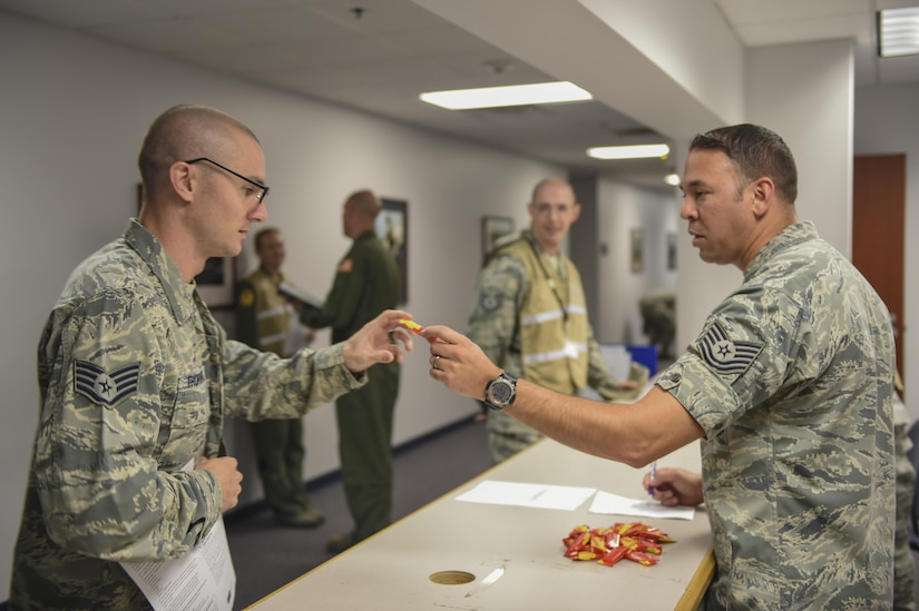 Staff Sgt. Bradley Thornton, 437th Maintenance Operations Squadron deficiency analyst, left, receives a pack of Starburst from Tech. Sgt. Hector Velazquezramos, 628th Medical Group diagnostics and therapeutic flight chief, right, at a point of distribution during a public health emergency exercise on Joint Base Charleston, South Carolina, Nov. 9, 2016. In the event of a real world incident, members would be given a flu vaccine if they hadn't already received one as well as medication to combat the outbreak. To simulate that, those who participated in the base wide virus exercise were given the vaccination and candy to represent the medication.