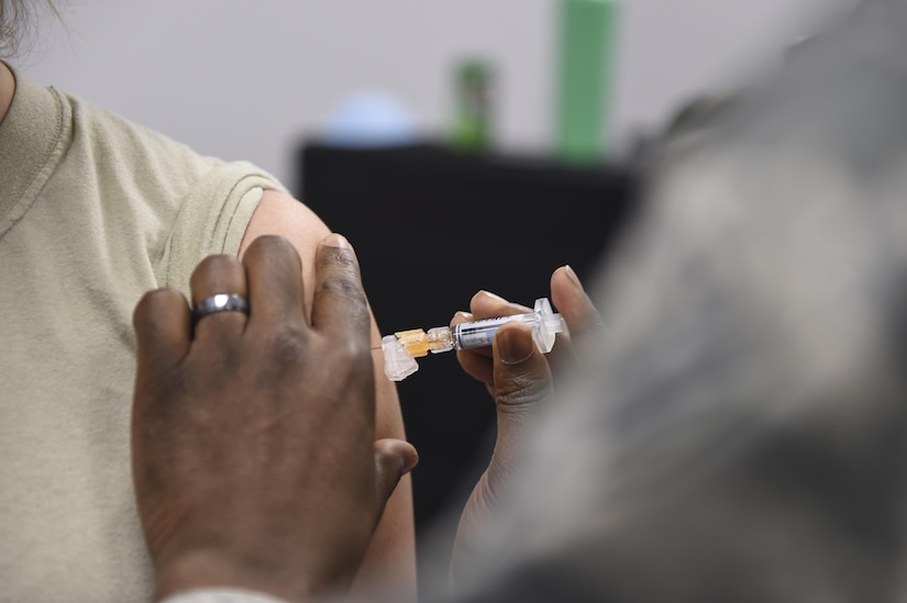 An annual flu vaccine is given to a member of Joint Base Charleston at a point of distribution during a public health emergency exercise on Joint Base Charleston, South Carolina, Nov. 9, 2016.  In the event of a real world incident, members would be given a flu vaccine if they hadn't already received one, as well as medication to combat the outbreak. To simulate that, those who participated in the exercise were given the vaccination and candy to represent the medication.
