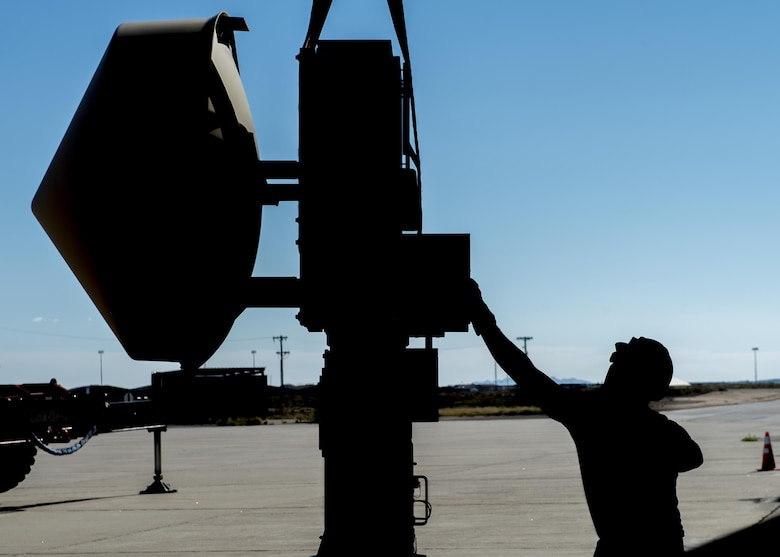 Senior Airman Jon, a 49th Aircraft Maintenance Squadron aircraft communications maintenance technician, balances and guides a Ground Data Terminal antenna into position before installation at Holloman Air Force Base, N.M., on Nov. 8, 2016. The GDT is an 800-pound antenna that facilitates communication between Remotely Piloted Aircraft and their crews on the ground in the Ground Control Station. (U.S. Air Force photo by Senior Airman Emily Kenney)