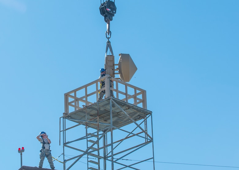Staff Sgt. Paul and Senior Airman Tyler, 49th Aircraft Maintenance Squadron aircraft communications maintenance technicians, affix a Ground Data Terminal to a platform riser at Holloman Air Force Base, N.M., on Nov. 8, 2016. The antenna was mounted on the roof of an existing hangar, a first for Holloman. (U.S. Air Force photo by Senior Airman Emily Kenney)
