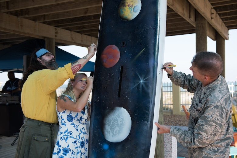 Brig. Gen. Wayne Monteith, 45th Space Wing commander, Sierra Gill and Duke Fortesque sign a sailboard during the 45th Space Wing's 25th Anniversary Celebration Nov. 10, 2016, at the Beach House at Patrick Air Force Base, Fla. Gill and Fortesque used their artistic skills to create a sailboard symbolizing the wing's storied history as the World's Premier Gateway to Space. (U.S. Air Force photo by Matthew Jurgens)