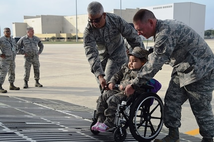 Tech. Sgt. Ernesto Compean, left, and Staff Sgt. Timothy McKay, right, Rising 6 members from the 433rd Aircraft Maintenance Squadron, help 5-year-old Mayra Salinas onto the front loading ramp of a C-5M Super Galaxy Nov. 5, 2016 at Joint Base San Antonio-Lackland, Texas. Mayra was chosen to be the Rising 6 Airman for the Day. The Rising 6 is a private organization comprised of Airmen grade E-1 through E-6. (U.S. Air Force photo/Tech. Sgt. Carlos J. Treviño)