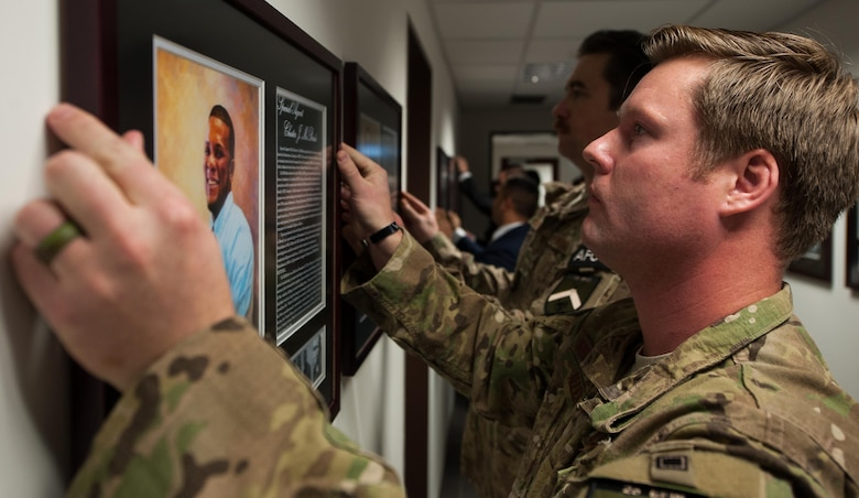 Special Agent Bradley Allen, 25th Expeditionary Field Investigation Squadron agent, hangs the portrait of a deceased Air Force Office of Special Investigations portrait during the 25th Expeditionary Field Investigation Squadron's fallen heroes dedication memorial at Ramstein Air Base, Germany, Nov. 10, 2016. The portraits contained biographies of the servicemember that told their story and the legacy they left behind. Veteran's Day is a celebration to honor America's veterans for their patriotism, love of country, and willingness to serve and sacrifice, even if it means their lives. According to a recent Congressional Research Service report, more than 6,500 U.S. service members have lost their lives in post-9/11 conflicts in Iraq and Afghanistan. (U.S. Air Force photo by Airman 1st Class Lane T. Plummer)