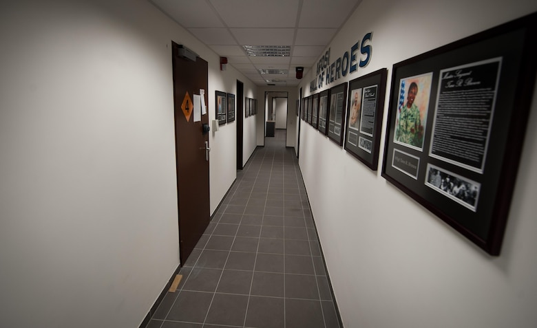 """Portraits of fallen Office of Special Investigations Airmen hang from the walls of the 25th Expeditionary Field Investigation Squadron's detachment at Ramstein Air Base, Germany, Nov. 10, 2016. The 25th EFIS constructed a """"Hall of Heroes,"""" dedicated to remembering OSI agents who lost their lives in the line of duty. Veteran's Day is a celebration to honor America's veterans for their patriotism, love of country, and willingness to serve and sacrifice, even if it means their lives. According to a recent Congressional Research Service report, more than 6,500 U.S. servicemembers have lost their lives in post-9/11 conflicts in Iraq and Afghanistan. (U.S. Air Force photo by Airman 1st Class Lane T. Plummer)"""
