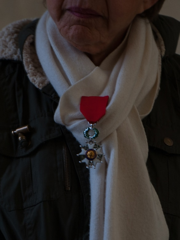 A woman awaits for the wreath laying ceremony to begin at the Lorraine American Cemetery to honor the deceased war veterans Nov. 11, 2016, at St. Avold, France. Pinned to her scarf is her deceased husband's Legion of Merit medal, awarded to U.S. servicemembers for exceptionally meritorious conduct in the performance of outstanding services and achievements. Veteran's Day is observed annually on November 11 and commemorates military veterans who currently serve or have served the U.S. armed forces, including those who gave the ultimate sacrifice. According to the DoD and Veterans Administration, since World War I, approximately 624,000 U.S. servicemembers have been killed in action battling in wars and conflicts. The Lorraine American Cemetery contains the buried remains of over 10,000 of them. It is the largest burial site of U.S. servicemembers in Europe. (U.S. Air Force photo by Airman 1st Class Lane T. Plummer)