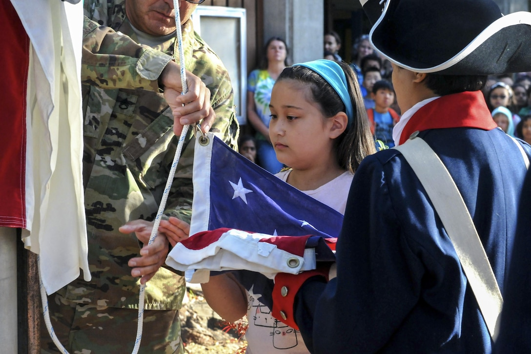 Amy Pietromanco helps raise the U.S. flag during a flag-raising ceremony at Christa McAuliffe Elementary School in Saratoga, Calif., Nov. 10, 2016. Army Staff Sgt. Juan Martinez, left, and Sgt. Arleen Banioza, right, assisted the fourth grader. Martinez, a human resources specialist, and Banioza, a color guard noncommissioned officer, are assigned to the 63rd Regional Support Command. Army photo by Alun Thomas