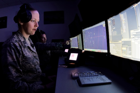 The faces of Capt. Jennifer and Maj. Michael (last names not used in accordance with Air Combat Command directives), 752nd Operation Support Squadron air battle managers, are illuminated by the glow of their computer screens as they follow and point out target aircraft during a training scenario on the AN/TYQ-23A emulator Oct. 31, 2016, Tinker Air Force Base, Okla. The trainees are working as part of a larger crew to test the communication and decision making skills of the individuals and team under a stressful environment. (Photos taken of systems configured to unclassified status by subject matter experts. Photo has been manipulated to blur the names of individuals shown.)(U.S. Air Force photo/Greg L. Davis)