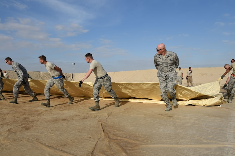 The 380th Expeditionary Logistics and Readiness Squadron come together to lay out a new 210,000 gallon fuel bladder at an undisclosed location in Southwest Asia, Nov. 9, 2016. The Fuels Management Flight maintains 27 bladders and two underground tanks holding JP-8 jet fuel in addition to other bladders and tanks containing five other fuels. (U.S. Air Force photo by Tech. Sgt. Christopher Carwile)