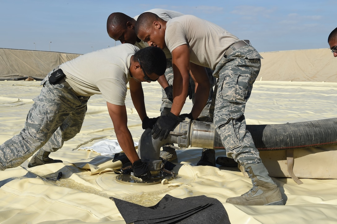 380th Fuels Management Flight members latch a fuel hose onto the new JP-8 jet fuel bladder that was installed at an undisclosed location in Southwest Asia, Nov. 9, 2016. This bladder will hold 210,000 gallons of jet fuel once fully connected, becoming part of a network of 27 similar bladders providing fuel to the 380th Air Expeditionary Wing flying mission. (U.S. Air Force photo by Tech. Sgt. Christopher Carwile)