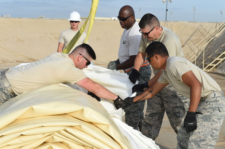 Members of the 380th Expeditionary Logistics Readiness Squadron remove the protective shipping cover from a new fuel bladder at an undisclosed location in Southwest Asia, Nov. 9, 2016. The cover has to be removed before crane operators leave in case the bladder needs to be moved so that it rolls out in the correct direction. (U.S. Air Force photo by Tech. Sgt. Christopher Carwile)