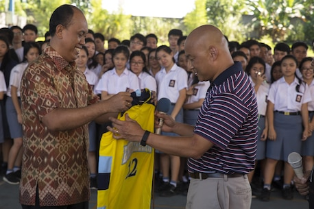 U.S. Navy Lt. Cmdr. Philip Park, right, command chaplain with Marine Aircraft Group 12, recieves a school basketball jersey from Jemmy Jermias, the school principal, during a visit at Sekolah Menengah Eben Haezar Manado High School in Manado, Indonesia, Nov. 9, 2016. The exchanging of gifts symbolizes each other's appreciation for cultural exchanges and community relations events. As part of a community relations event, the visit offered Marines and Sailors with Marine All-Weather Fighter Attack Squadron (VMFA(AW)) 225 the opportunity to engage in cultural exchanges and build relationships within the local community. (U.S. Marine Corps photo by Cpl. Aaron Henson)
