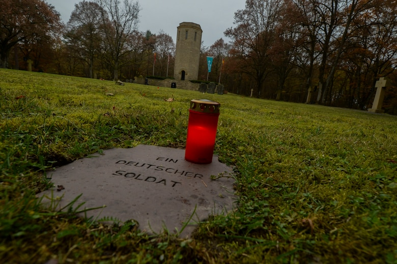 A candle remains lit on top of a grave marker of an unknown German soldier before a German National Day of Mourning observance ceremony at the Kolmeshöhe Military Cemetery in Bitburg, Germany, Nov. 13, 2016. The day, known as Volkstrauertag in German, observes the human cost of warfare and suffering.  (U.S. Air Force photo by Staff Sgt. Joe W. McFadden)