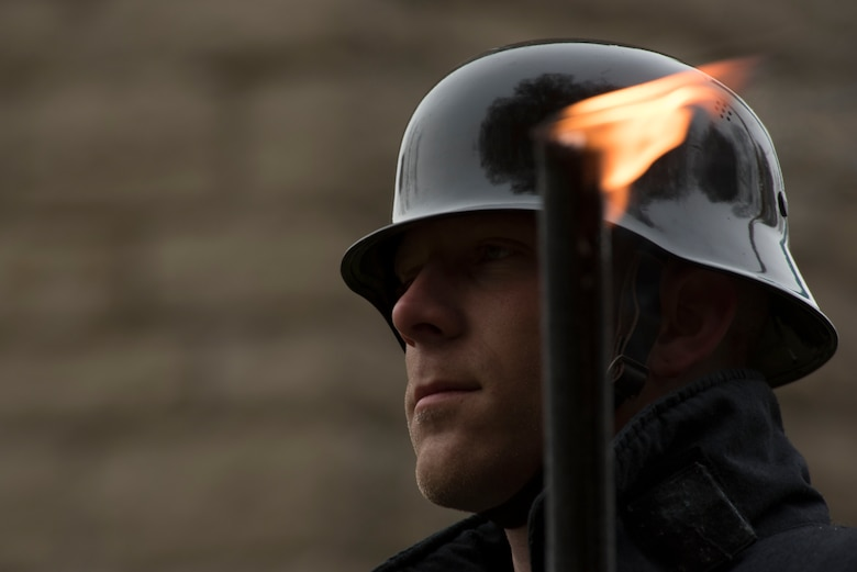 A German soldier donning a traditional Germany army helmet holds a torch during a German National Day of Mourning observance ceremony at the Kolmeshöhe Military Cemetery in Bitburg, Germany, Nov. 13, 2016. The day, known as Volkstrauertag in German, observes the human cost of war and was established following the conclusion of the First World War. (U.S. Air Force photo by Staff Sgt. Joe W. McFadden)