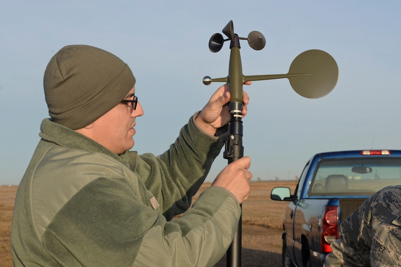 Tech. Sgt. James Pomar, 5th Operations Support Squadron missions NCO in charge, attaches a wind mast to a tactical meteorological equipment base at Minot Air Force Base, N.D., Nov. 8, 2016. The equipment provides weather flight with wind and speed direction data to inform operations personnel of inclement weather. (U.S. Air Force photo/Airman 1st Class Jessica Weissman)