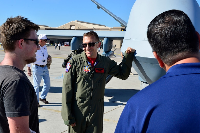Capt. Michael, 432nd Wing MQ-1 pilot, explains the capabilities of an MQ-9 Reaper during Aviation Nation Nov. 11, 2016, at Nellis Air Force Base, Nevada. The MQ-1 Predator and MQ-9 Reaper were among the many other fighter, bombers, and legacy aircraft on display. (U.S. Air Force photo by Senior Airman Christian Clausen/Released)