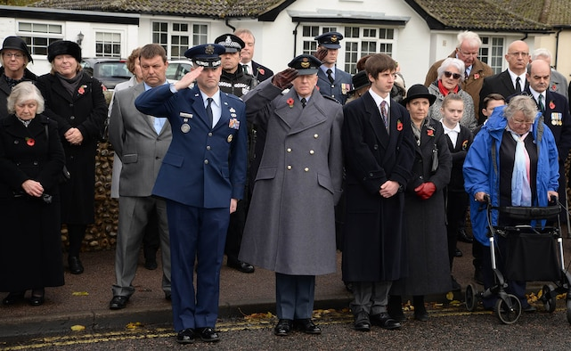 """U.S. Air Force Lt. Col. Ryan White, 100th Maintenance Group deputy commander, left of center, and Sqdn. Ldr. Richard Fryer, center, RAF Mildenhall station commander, salute during the playing of """"The Last Post"""" at the Remembrance Sunday parade Nov. 13, 2016, in Mildenhall, England. U.S. Air Force Airmen from RAF Mildenhall took part in the event along with Sea Cadets, Army Cadets, Air Cadets and other groups from the local community. Remembrance ceremonies are held around the U.K. each year on the closest Sunday to Armistice Day, Nov. 11, to honor those who lost their lives in wars both past and present. (U.S. Air Force photo by Karen Abeyasekere)"""