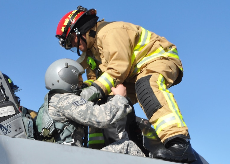 Tech. Sgt. Gabe Ulibarri, 944th Civil Engineer Squadron firefighter, helps to extricate an Airman from a simulated burning F-16, during annual egress training during the November UTA. (U.S. Air Force photo by Tech. Sgt. Barbara Plante)