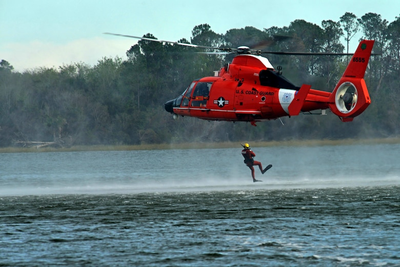 A U.S. Coast Guardsman jumps out of an MH-65 Dolphin at Coast Guard Station Tybee, Ga., Nov. 8, 2016. The helicopter crew and the swimmer played a part in water survival training for 20th Fighter Wing pilots assigned to Shaw Air Force Base, S.C. (U.S. Air Force photo by Airman 1st Class Destinee Sweeney)