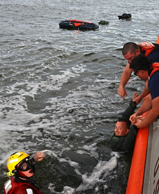 Two U.S. Coast Guardsmen pull Air Force Lt. Col. Martin Mentch, 20th Fighter Wing director of staff, onto a 45-foot response boat-medium at Coast Guard Station Tybee, Ga., Nov. 8, 2016. 20th FW pilots participated in water survival training, simulating an aircraft ejection and helicopter rescue. (U.S. Air Force photo by Airman 1st Class Destinee Sweeney)