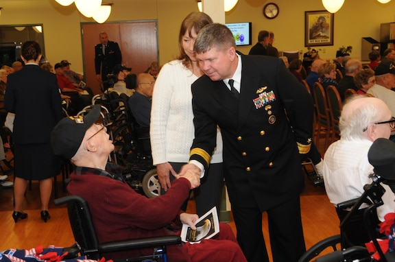 """Deputy Commander of U.S. Strategic Command's (USSTRATCOM) Joint Functional Component Command for Global Strike, Rear Adm. Thomas E. Ishee (right), and his wife Jerrilyn Ishee, greet U.S. Army WWII veteran Paul Curtis during Eastern Nebraska Veterans' Home annual Veterans Day program in Bellevue, Neb., Nov. 11, 2016.  The program celebrated the residents who live there along with veterans worldwide. Veterans Day was originally referred to as """"Armistice Day"""" because it was celebrated on the same date that World War I hostilities ended on the 11th hour of the 11th day of the 11th month in 1918. On June 1, 1954, President Dwight D. Eisenhower officially changed the name to Veterans Day, celebrated on Nov. 11 each year, a day to honor American veterans of all wars. (USSTRATCOM photo by Steve Cunningham)"""