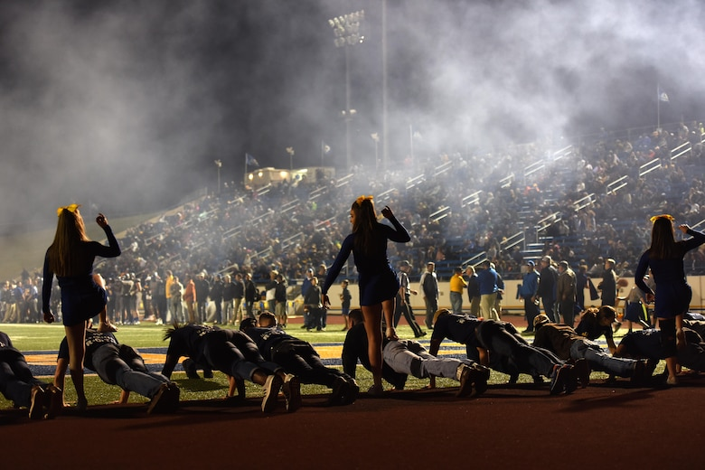 Angelo State University cheerleaders mock step on Junior ROTC units at the ASU Military Appreciation football game at San Angelo Stadium, Texas, Nov. 12, 2016. The Junior ROTC cadets performed pushups every time ASU scored a touchdown. (U.S. Air Force photo by Airman 1st Class Caelynn Ferguson/Released)