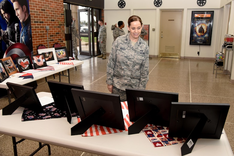 U.S. Air Force Capt. Tanda Holden, 17th Training Wing executive officer, observes the Hands Display at the base theater on Goodfellow Air Force Base, Texas, Nov. 10, 2016. The family advocacy office displayed the hands before a commander's call to maximize awareness for local veterans. (U.S. Air Force photo by Senior Airman Joshua Edwards/Released)