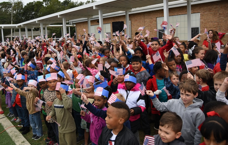 Students at Jeff Davis Elementary School wave their flags during a Veterans Day celebration Nov. 11, 2016, in Biloxi, Miss. During the event, students delivered the Pledge of Allegiance and sang several patriotic songs. Keesler Air Force Base leadership, Honor Guard Airmen and personnel attended the event. (U.S. Air Force photo by Kemberly Groue/Released)