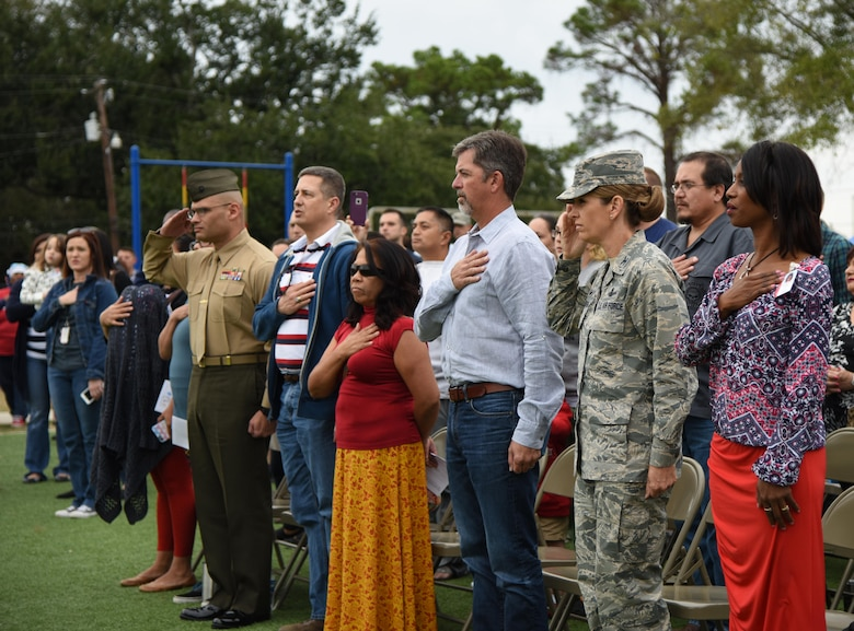 Col. Michele Edmondson, 81st Training Wing commander, and fellow audience members honor the flag during a Jeff Davis Elementary School Veterans Day Celebration Nov. 11, 2016, in Biloxi, Miss. During the event, students also sang several patriotic songs. Keesler Air Force Base Honor Guard Airmen also participated in the event. (U.S. Air Force photo by Kemberly Groue/Released)