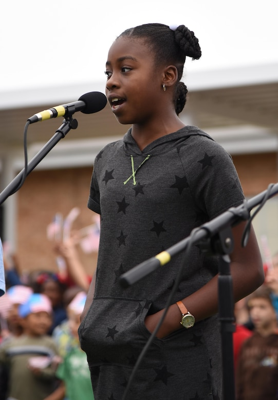 "Aysiah Sims, daughter of Maj. Jahayra Lowe, 81st Comptroller Squadron commander, sings the ""Allegiance Rap"" song during a Jeff Davis Elementary School Veterans Day Celebration Nov. 11, 2016, in Biloxi, Miss. During the event, students delivered the Pledge of Allegiance and sang several patriotic songs. The Keesler Honor Guard and other service members also participated in the event. (U.S. Air Force photo by Kemberly Groue/Released)"