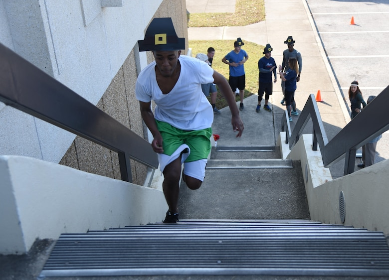 Senior Airman Martin Githui, 81st Contracting Squadron contracting specialist, leads his team in a staircase relay race at the Sablich Center during the Dragon Week Dragon Hunt Nov. 14, 2016, on Keesler Air Force Base, Miss. The scavenger hunt, consisting of six teams, kicked-off a week filled with resiliency and teambuilding events. (U.S. Air Force photo by Kemberly Groue/Released)