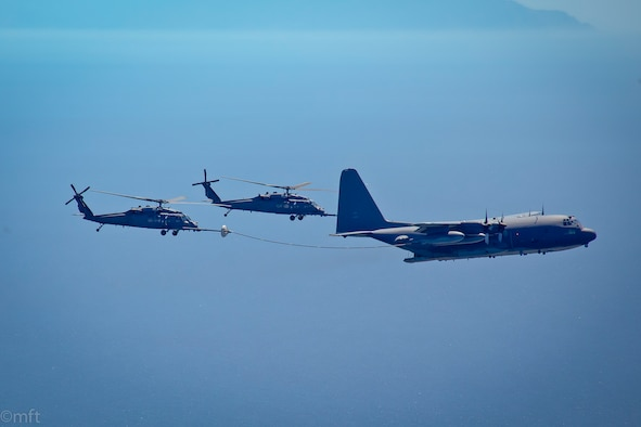 Two HH-60G Pave Hawk rescue helicopter and an MC-130P Combat Shadow aircraft, assigned with the 129th Rescue Wing, California Air National Guard, conduct an aerial refuel operations over the pacific ocean, April 3, 2014.  (Courtesy photo by Master Sgt. Miguel Toro/released)