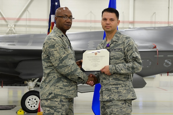 Electronic Warfare Specialist Staff Sgt. Jesus Soto receives a Purple Heart from 388th Component Maintenance Sqaudron Commander Lt. Col. Steven Oliver at Hill Air Force Base, Utah, Oct. 30, 2015. Soto was injured in 2005 while deployed with the 1st Security Forces Squadron to Forward Operating Base Speicher near Tikrit, Iraq. While there, he provided security to U.S. convoys and foreign national supply trucks. (U.S. Air Force photo by R. Nial Bradshaw/Released)