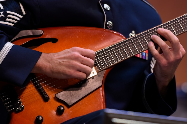 An Airmen of Note member strums the guitar at the Jazz Heritage Series at the Rachel M. Schlesinger Concert Hall in Alexandria, Va., Nov. 11, 2016. The Airmen of Note played alongside a legendary jazz artist. Each year the series is broadcasted to millions over National Public Radio, independent jazz radio stations, satellite radio services and the Internet. (U.S. Air Force photo by Airman 1st Class Valentina Lopez)