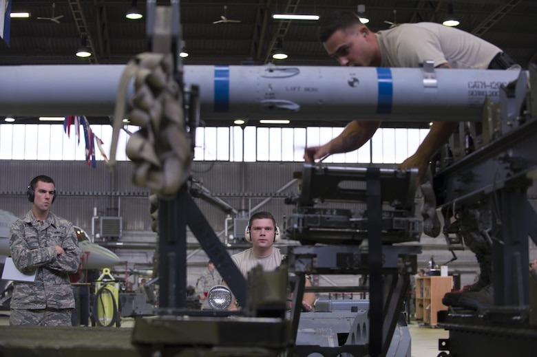 Evaluators observe Staff Sgt. Daniel Vazquez, left, and Airman 1st Class Christian Edson, right, both 52nd Aircraft Maintenance Squadron tactical aircraft weapons systems specialist, as Edson positions the MJ-IC jammer boom during the 52nd Fighter Wing Load Crew of the Quarter competition Nov. 10, 2016. The load crew competition required two teams of three competing members to load weapons to the wings of an F-16 Fighting Falcon as quickly and accurately as possible. (U.S. Air Force photo by Senior Airman Dawn M. Weber)