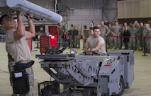 U.S. Air Force Staff Sgt. Daniel Vazquez, left, and Airman 1st Class Christian Edson, right, both 52nd Aircraft Maintenance Squadron tactical aircraft weapons systems specialist, members of one of the load competition teams work to load a dummy weapon on to an F-16 Fighting Falcon during the quarterly weapons load competition in Hangar One on Spangdahlem Air Base, Germany, Nov. 10, 2016. Family, friends and members of the Spangdahlem community attended the competition to see which of the two teams of three maintenance Airmen would move on to the annual load competition. (U.S. Air Force photo by Senior Airman Dawn M. Weber)