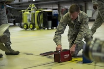 U.S. Air Force Airman 1st Class Austin Winker, 52nd Aircraft Maintenance Squadron weapons load crew member, identifies parts before loading inert weapons during the quarterly weapons load competition in Hangar One at Spangdahlem Air Base, Germany, Nov. 10, 2016. Family, friends and coworkers watched as two teams competed against each other for a spot in the annual load competition. (U.S. Air Force photo by Airman 1st Class Preston Cherry)