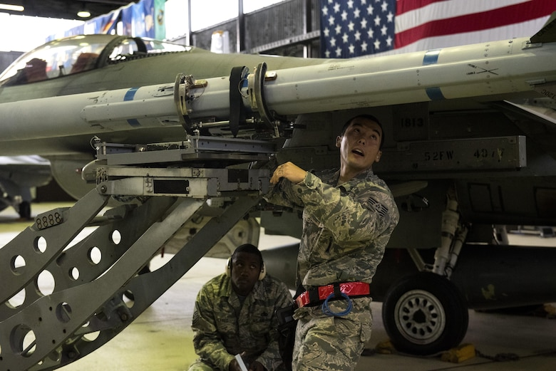U.S. Air Force Tech. Sgt. Robert Morley, right, 52nd Aircraft Maintenance Squadron weapons load crew chief, loads an inert weapon on an F-16 Fighting Falcon during the quarterly weapons load competition in Hangar One at Spangdahlem Air Base, Germany, Nov. 10, 2016. The competition consisted of two teams competing against each other to load weapons quickly and accurately. (U.S. Air Force photo by Airman 1st Class Preston Cherry)