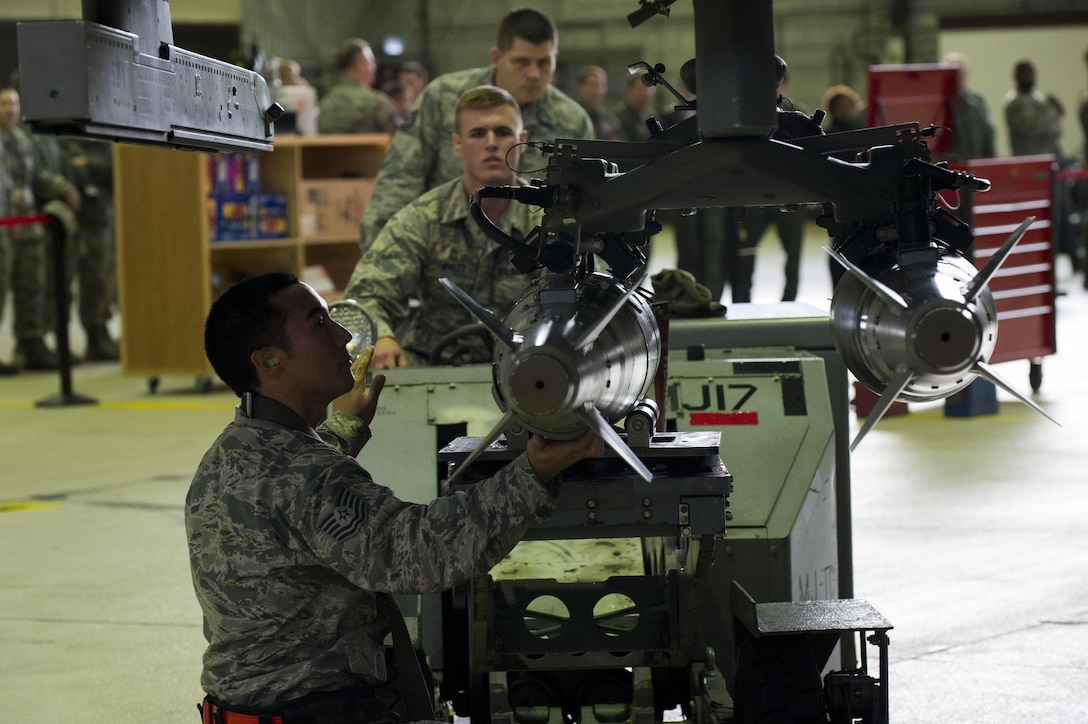 U.S. Air Force Airman 1st Class Austin Winker, center, 52nd Aircraft Maintenance Squadron weapons load crew member, and Tech. Sgt. Robert Morely, left, 52nd Aircraft Maintenance Squadron weapons load crew chief, load inert missiles on an F-16 Fighting Falcon during the quarterly weapons load competition in Hangar One at Spangdahlem Air Base, Germany, Nov. 10, 2016. Load crew members competed against the clock and each other to load an F-16 with fewer discrepancies than their competitor. (U.S. Air Force photo by Airman 1st Class Preston Cherry)