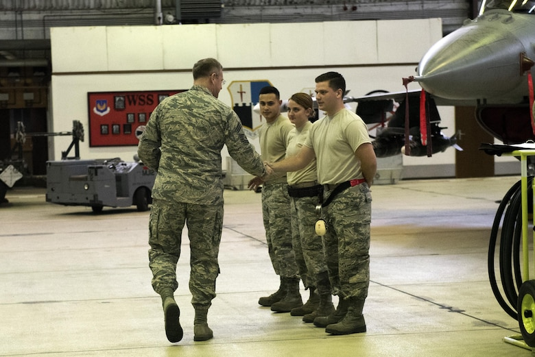 U.S. Air Force Chief Master Sgt. Craig Brandenburg, left, 52nd Maintenance Group wing weapons manager, congratulates the winning Aircraft Maintenance Squadron load crew members during the quarterly weapons load competition in Hangar One at Spangdahlem Air Base, Germany, Nov. 10, 2016. The competition consisted of two teams, each with three load crew members, competing for a spot in the annual load competition.  (U.S. Air Force photo by Airman 1st Class Preston Cherry)