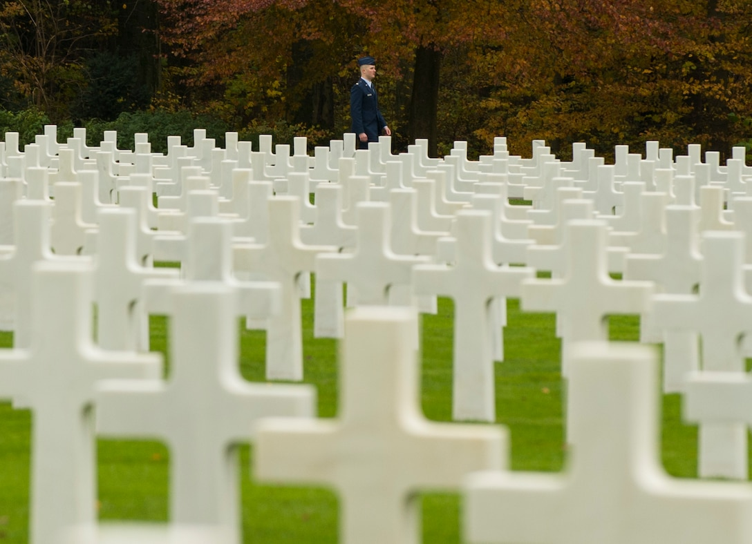 A U.S. Air Force Airman walks among white marble crosses and stars marking the burial sites of American service members at the Luxembourg American Cemetery and Memorial in Hamm, Luxembourg City, Luxembourg, Nov. 11, 2016. Approximately 5,076 U.S. service members who died during World War II are buried at this site. (U.S. Air Force photo by Senior Airman Dawn M. Weber)