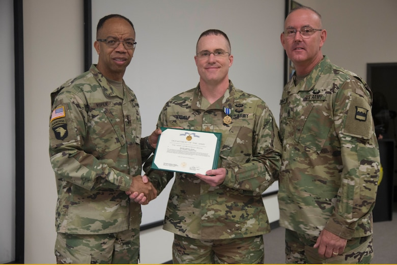 Maj. Gen. A.C. Roper, commander of the 80th Training Command, and Command Sgt. Maj. Jeffrey Darlington, command sergeant major of the 80th, present Maj. Jason Nagel with the Army Achievement Medal for earning top honors as the Officer Instructor of the Year at the 80th's 2016 IOY competition at Fort Knox, Ky., Oct. 23, 2016. Photo by Spc. Sarah Ruiz, 55th Signal Company (Combat Camera).