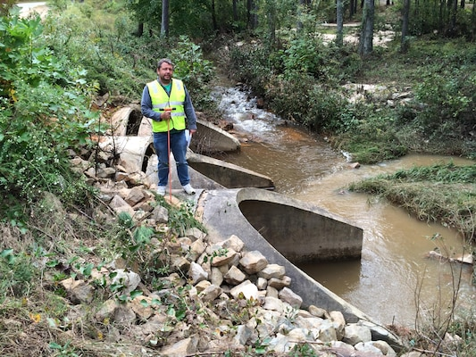 Patrick Hager, a Savannah District structural engineer, stands above a water crossing during infrastructure assessments conducted at Fort Bragg in North Carolina Oct. 14, 2016. The water crossing consists of three concrete culverts that direct the outflow from a connected lake. The inlet caps on the upstream side separated from concrete pipes but showed no considerable damage.