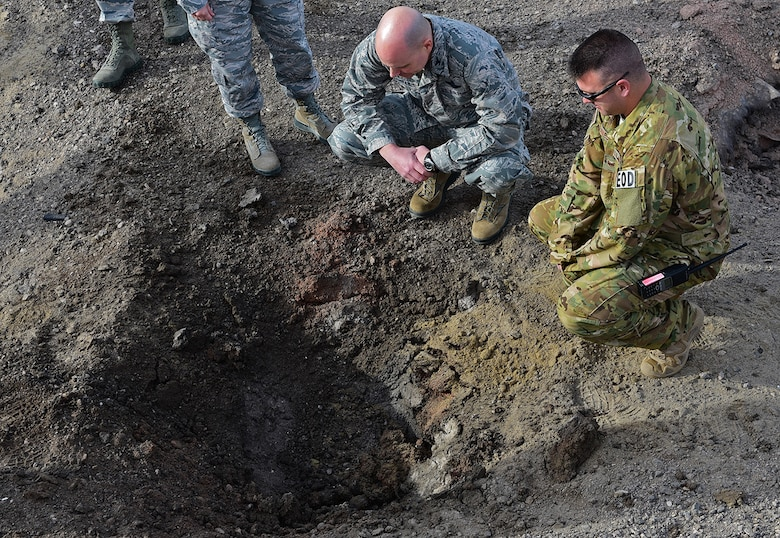Col. Bradley Cochran, vice commander of the 28th Bomb Wing, examines the crater left from the explosives he triggered at Ellsworth Air Force Base, S.D., Nov. 14, 2016. The hole was created by less than five pounds of explosives, which demonstrates the impact small improvised explosive devices can cause. (U.S. Air Force photo by Airman 1st Class James L. Miller)