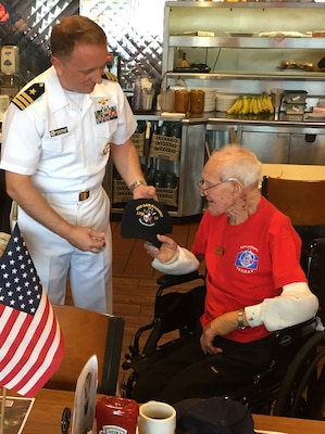 In celebration of his 100th birthday, Naval Aviator, Cmdr. Jeffrey Reynolds, executive officer, Navy Recruiting District San Antonio, presented a USS SAN ANTONIO (LPD-17) command ball cap to WWII Naval Aviator, Lt. Glen Shean during an Alamo Honor Flight Breakfast held at Denny's, Nov. 7.   Shean, a Boerne resident and native of Cordell, Okla., served in the Navy as a TBF Avenger pilot from May 7, 1942 thru Oct. 1, 1946 aboard the USS Card (CVE-11), a Bogue-class escort aircraft carrier.