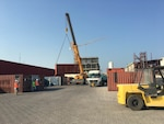 A crane at DLA Distribution Bahrain prepares to load one of the first of five trucks that will be transporting supplies using the emerging Trans-Arabian Network routes.